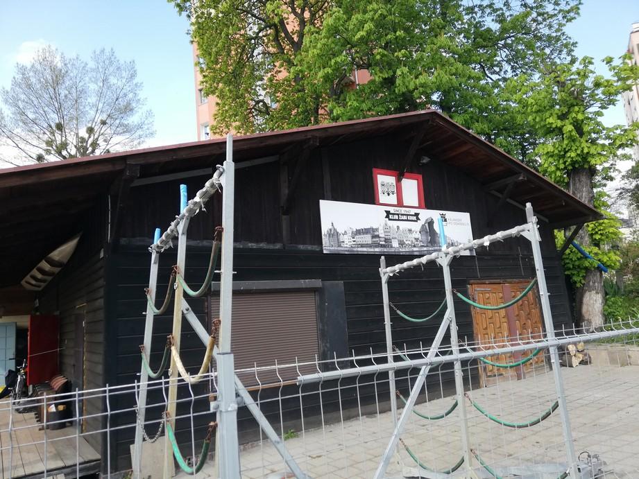 """Gdańsk. Przystań Żabi Kruk. Zdjęcia współczesne. Przedwojenny budynek przystani. Wykonany z drewna pomalowanego na ciemny brąz. Pod dachem bundynku zawieszona jest tablica ukazująca stare kamienice na Motławą na długości ulic Długie Pobrzeże oraz Rybackie pobrzeże, Bramę Żuraw, Bramę Świętego Ducha. Napisy: """"Klub Żabi Kruk Since 1947"""" oraz """"Kajakiem po gdańsku.pl""""."""