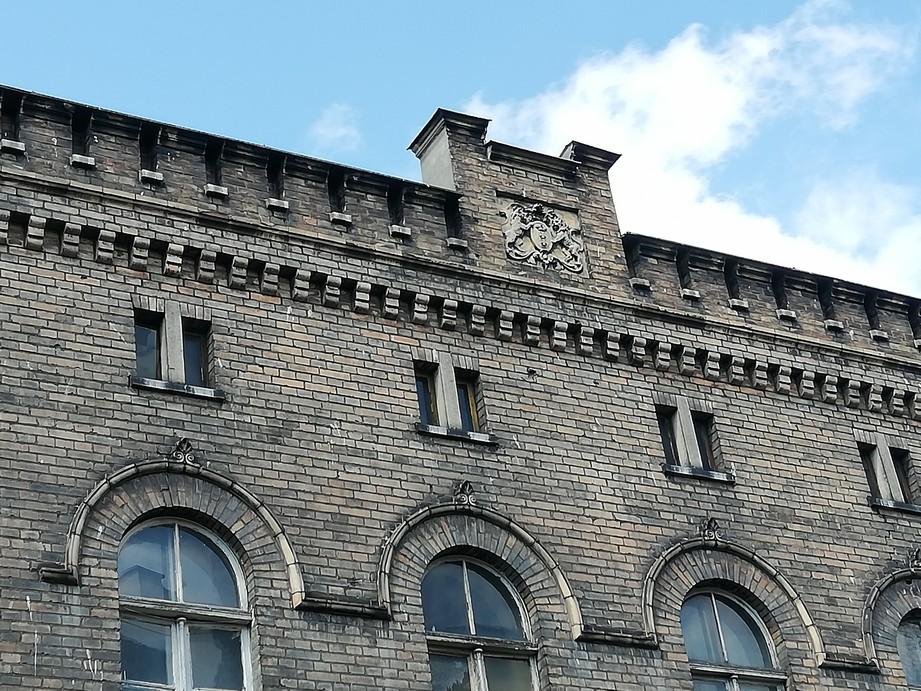 Gdańsk. Lombard miejski i Herb Gdańska. Zdjęcia współczesne. Na zdjęciu widnieje część reprezentacyjnej fasady bocznej ceglanego budynku, którą na szczycie zdobi herb gdańska (dwa lwy) wykuty w kamiennej płycie. Obiekt nie został odnowiony i posiada liczne ciemne zabrudzenia. Okna na pierwszym piętrze zakończone są łukiem. Budynek ten został zbudowany w stylu arkadowym. Okna na poddaszu są niewielkie i prostokątne.