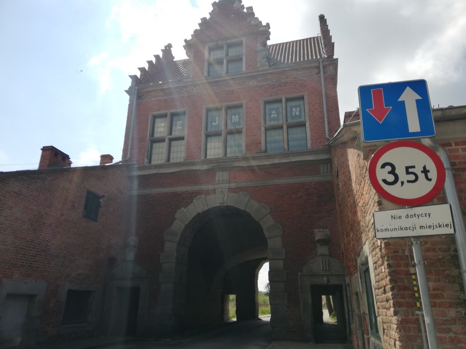 Gdańsk. Brama Nizinna od ul. Dolna Brama. Zdjęcia współczesne. Zdjęcie przedstawia ceglany budynek, który posiada szczegóły wykonane z jasnoszarego kamienia. W obiekcie znajduje się tunel zakończony łukiem, a po jego obu stronach (po lewej, jak i po prawej) umiejscowione są przejścia dla pieszych. Nad tunelem (na wysokości drugiego piętra) znajdują się trzy okna oraz jedno na poddaszu. Wszystkie otwory okienne są prostokątne, w kamiennych obokniach. Do budowli przylegają dwie symetryczne, murowane z cegły ściany budynków.