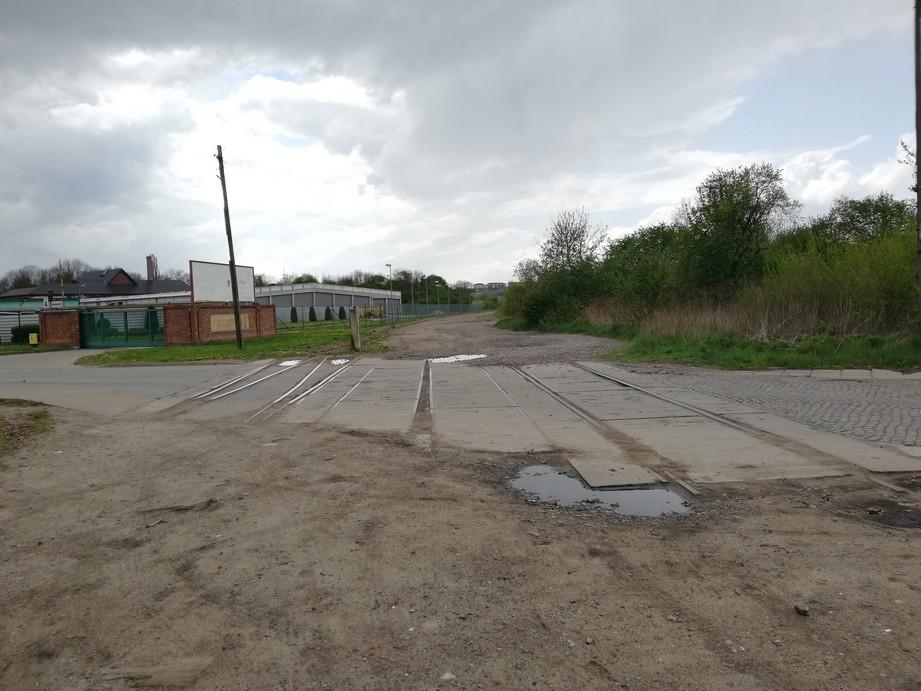 Gdańsk. Dworzec Południowy. Zdjęcia współczesne. Stare tory do Dworca Południowego. Na zdjęciu widać stare drogi. Środkowa droga jest wykonane z betonowych płyt, między którymi umieszczone są dawne tory. Jest to tylko fragment drogi – przed nią i za nią znajduje się droga gruntowa z kałużami. Po prawej stronie łączy się z nią droga zbudowana z kamiennej kostki brukowej, a po lewej nowoczesna droga asfaltowa. W tle występują budynki i drzewa liściaste.