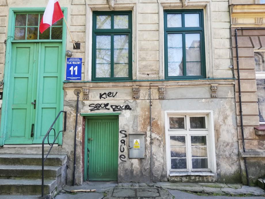 Gdańsk. Sklep kolonialny. Zdjęcia współczesne. Na zdjęciu znajduje się fragment zabytkowego budynku w kolorze pisaku. Na parterze znajdują się niewielkie drewniane zielone drzwi oraz białe drewniane okno. Na pierwsze piętro prowadzą kamienne schody, a przy nich znajduje się główne wejście – masywne drewniane zielone drzwi z górnym oknem. Na pierwszym piętrze umiejscowione są również dwa ciemnozielone drewniane okna.  Nad drzwiami i oknem można dostrzec fragmenty napisu, informującego, że w tej kamienicy znajdował się sklep kolonialny.