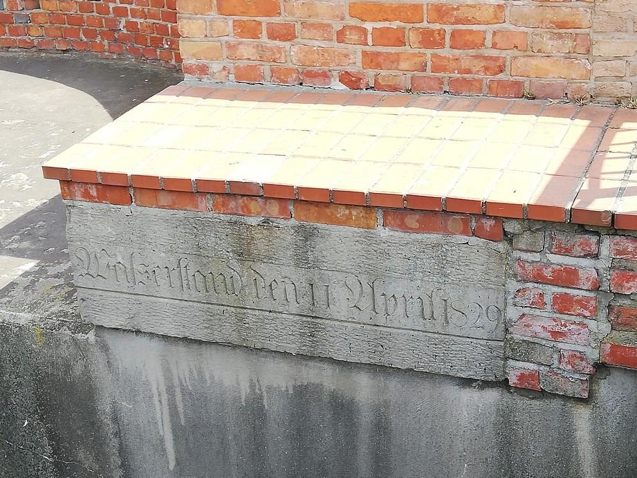 Gdańsk. Młyn zapasowy. Zdjęcia współczesne. Kamienna tablica, na której zaznaczono, dokąd sięgała woda podczas wielkiej powodzi w 1829 r. Na zdjęciu widać ceglany mur, na którym w miejscu gdzie znajduje się cement wyryty jest napis informujący o poziomie wody podczas powodzi w 1829 r.