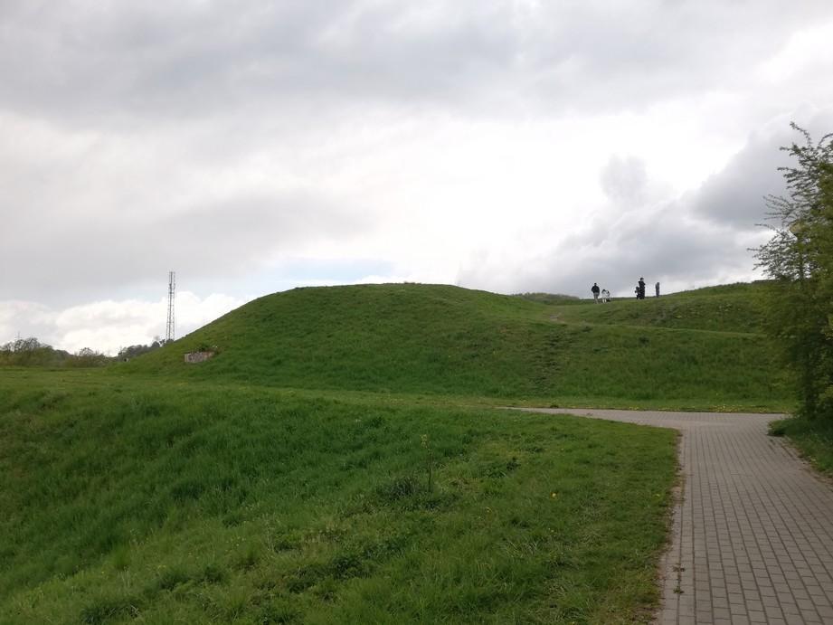 Gdańsk. Bastion św. Gertrudy. Zdjęcia współczesne. Na zdjęciu widać niewielkie wzniesienie porośnięte tylko trawą. Na szczyt wzniesienia prowadzi wydeptana ścieżka. Na wzniesieniu znajduje się kilka osób. Przed wzniesieniem umiejscowiony jest brukowany, szary chodnik.