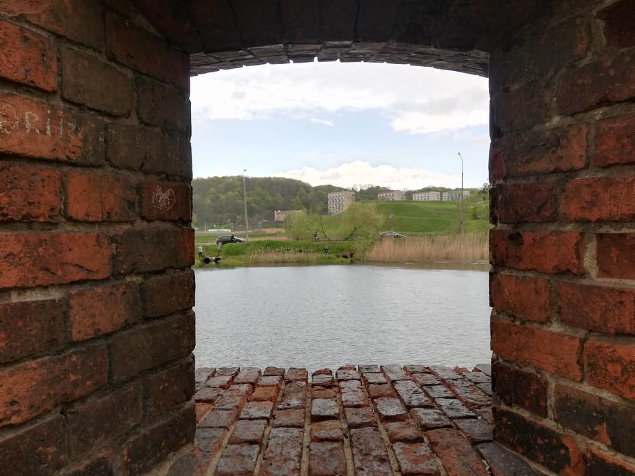 Gdańsk. Bastion św. Gertrudy. Zdjęcia współczesne. Zdjęcie przedstawia widok na bastion św. Gertrudy z okna starego ceglanego budynku. Na zdjęciu widać rzekę i trawiaste wzgórze, a w tle bloki mieszkalne oraz las.