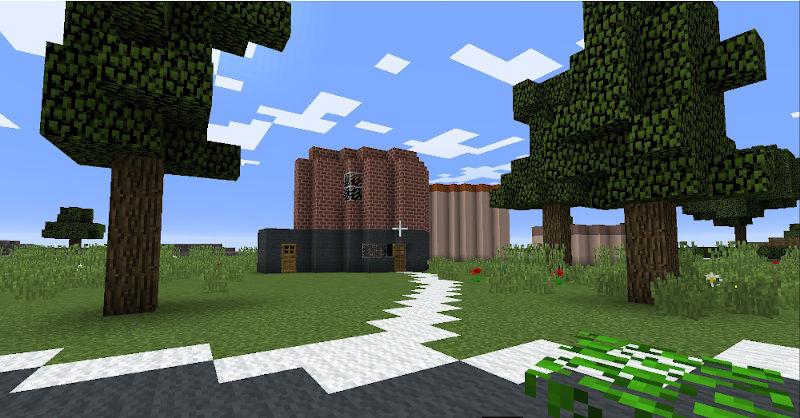 Gdańsk. Piekarnia Majchrowskiego. Minecraft: wizualizacja. Na zdjęciu znajduje się budynek, który u podstawy został stworzony z ciemnoszarych bloków, a powyżej z bloków ceglanych. Obiekt ma kształt kostki z niewielką dobudówką po lewej stronie. Na parterze znajdują się drewniane drzwi wejściowe oraz niewielkie okno. Na pierwszym piętrze znajduje się jedno okno. Dookoła budynku widnieje trawnik oraz kilka drzew i czerwonych kwiatków.