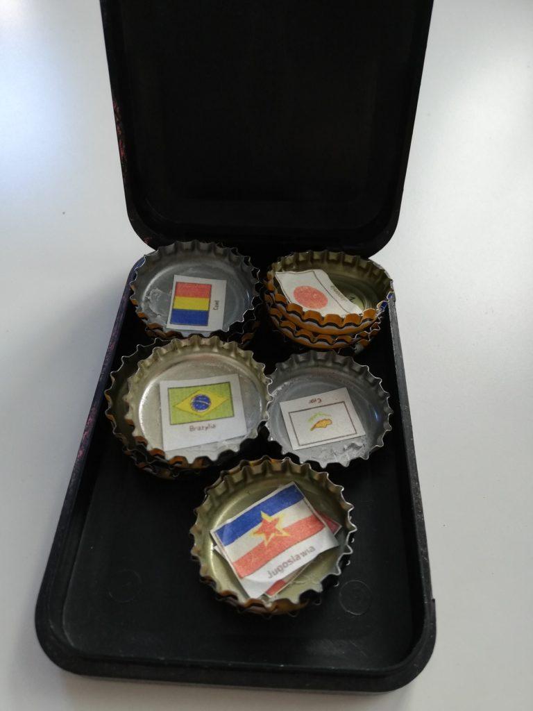 Zdjęcie przedstawia czarny otwierany pojemnik, w którym znajdują się kapsle z butelek. Do kapsli po wewnętrznej stronie zostały przyklejone niewielkie karteczki z wydrukowanymi kolorowymi flagami państw oraz ich nazwy: Japonia, Brazylia, Cypr, Jugosławia.