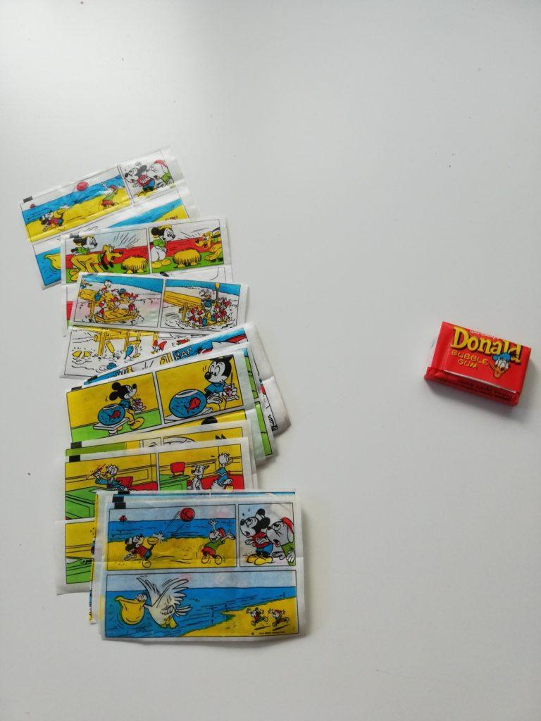 """Na zdjęciu znajduje się kolekcja różnych historyjek z gum Donald. Widnieją na nich takie postacie jak: Myszka Miki, Kaczor Donald, Pies Pluto. Na zdjęciu znajduje się również oryginalnie zapakowana stara guma Donald. Opakowanie jest w kolorze czerwonym z żółtym napisem """"Donald Bubble Gum"""" i wizerunkiem (głową) Kaczora Donalda."""