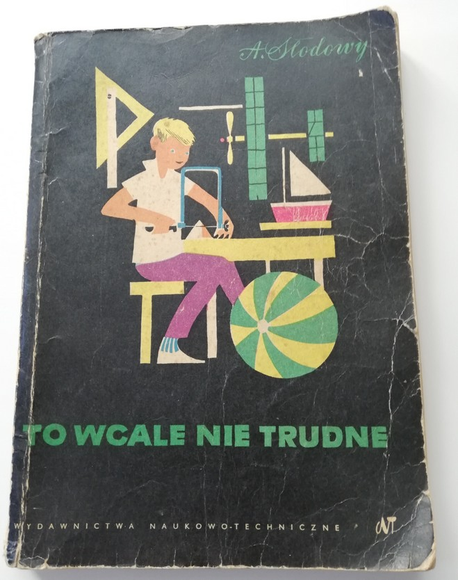 """Zdjęcie przedstawia okładkę książki pod tytułem """"To wcale nie trudne"""" autorstwa Adama Słodowego. Okładka ma kolor czarny, tytuł jest zielony, a na środku znajduje się kolorowa ilustracja chłopca siedzącego przy warsztacie i trzymającego piłę i kawałek drewna."""
