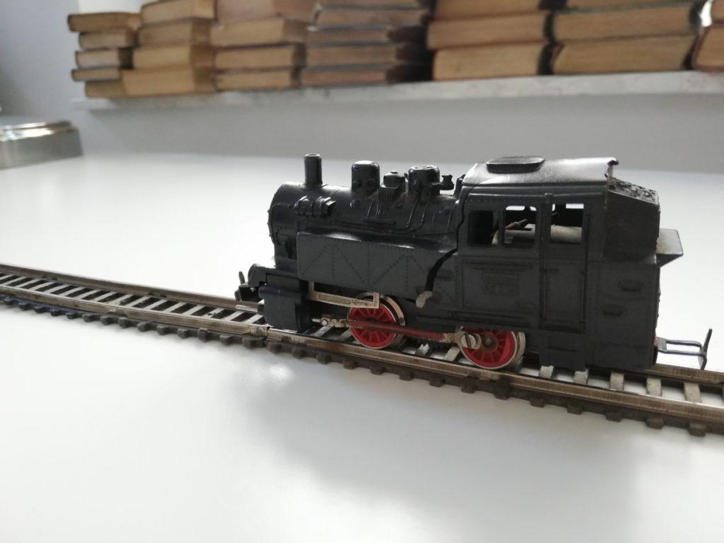 Zdjęcie przedstawia zabawkę-lokomotywę znajdującą się na torach. Lokomotywa jest czarna z czerwonymi kołami. Tory mają kolor brązowy. W tle leżą różne książki.