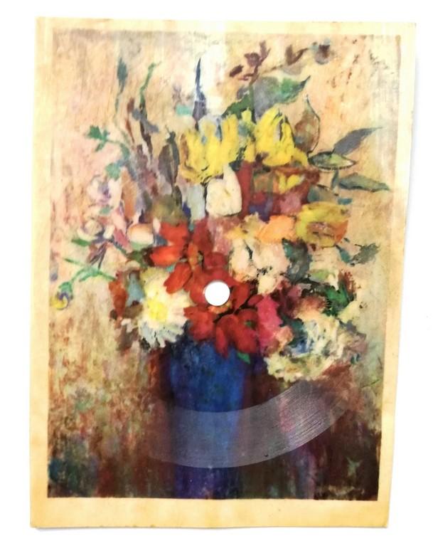 Zdjęcie przedstawia pocztówkę dźwiękową (odmiana płyty gramofonowej) z nadrukowanym obrazem kolorowych kwiatów w niebieskim wazonie.