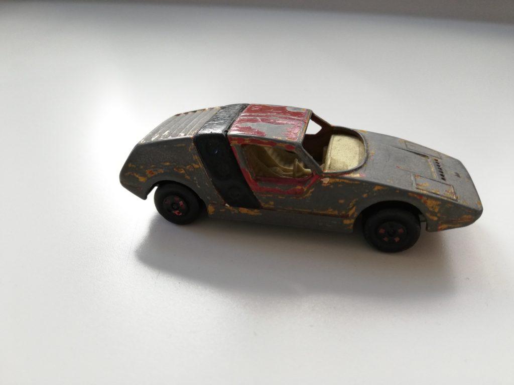 Zdjęcie przedstawia mocno zniszczoną zabawkę-samochodzik. W niektórych miejscach pozostała farba w kolorze czerwonym, czarnym i białym. Autko nie ma szybek. W środku znajduje się wnętrze w kolorze piaskowym – dwa fotele i kierownica. Koła w kolorze czarnym.