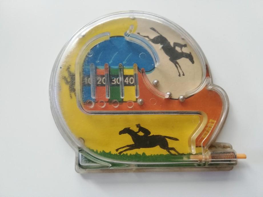 Zdjęcie przedstawia plastikową zabawkę – labirynt dla metalowych kulek. Na dole znajduje się patyczek ze sprężyną, dzięki któremu można wybić kuleczki w górną część labiryntu. Pod przezroczystym plastikowym labiryntem znajduje się kolorowy nadruk z jeźdźcami na koniach. Na samej górze labiryntu są mieszczone cztery kieszonki na piłeczki z nadrukowanymi punktami: 10, 20, 30 ,40.