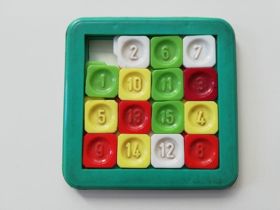 Zdjęcie przedstawia plastikową, kolorową zabawkę, która składa się z zielonej ramki i kwadracików w środku. Każdy kwadracik ma własną liczbę. Kwadraciki są ze sobą połączone, w taki sposób, aby było możliwe ich przesuwanie. Jeden kwadracik jest pusty, aby było miejsce na przesuwanie reszty plastikowych kwadracików.