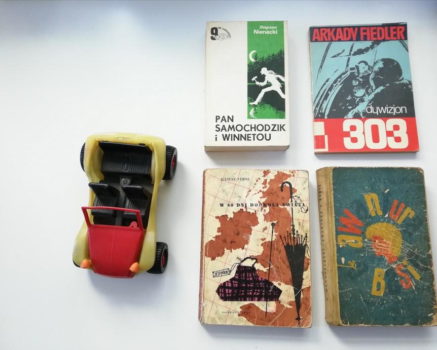 """Zdjęcie przedstawia plastikowy samochodzik, którego karoseria jest w kolorze czerwonym oraz żółtym. Wnętrze pojazdu oraz koła są w kolorze czarnym. Niedaleko od samochodziku ułożono cztery stare i lekko zniszczone książki: """"Pan samochodzik i Winnetou"""", """"Dywizjon 303"""", """"W 80 dni dookoła świata"""", """"Awantura o Basię""""."""