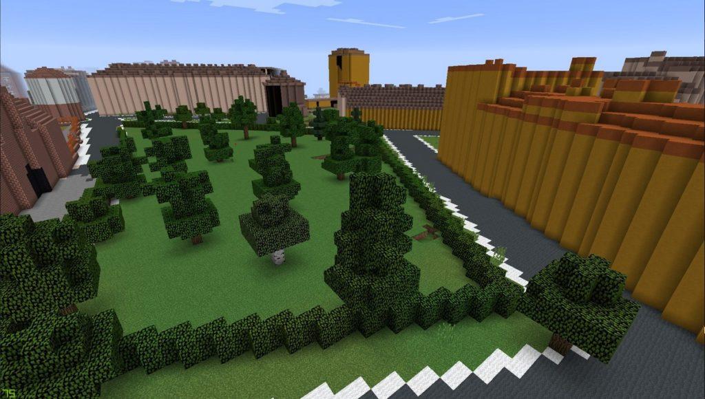 Gdańsk. Plac Wałowy. Wizualizacja w grze Minecraft. Na zdjęciu widnieje plac stworzony z zielonych bloków wraz z licznymi drzewami. Plac otoczony jest ulicami zbudowanymi z szarych bloków. Dookoła umiejscowione są budynki.