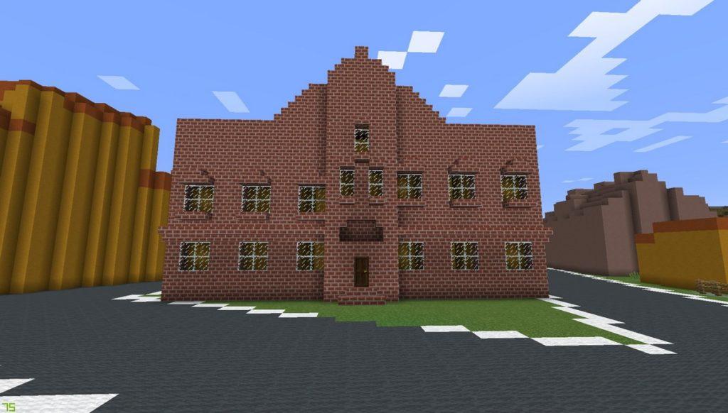 Gdańsk. Lombard miejski. Minecraft: wizualizacja. Zdjęcie przedstawia przód budynku wykonanego z ceglanych bloków. Obiekt posiada liczne okna. Otacza go droga stworzona z ciemnoszarych bloków. W tle znajdują się budynki.