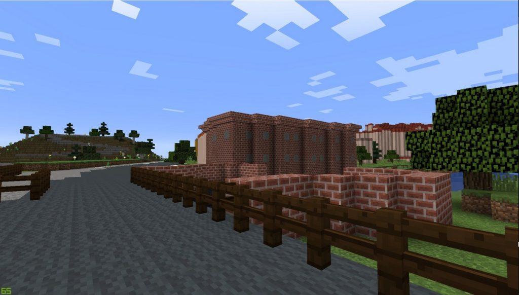 Gdańsk. Młyn zapasowy. Wizualizacja w grze Minecraft. Na zdjęciu widać stary, niski (dwu piętrowy) ceglany budynek bez okien, ceglany mur oraz most znajdujący się nad rzeką. W tle widać stare i nowe kamienice, drzewa i niewielką górkę.