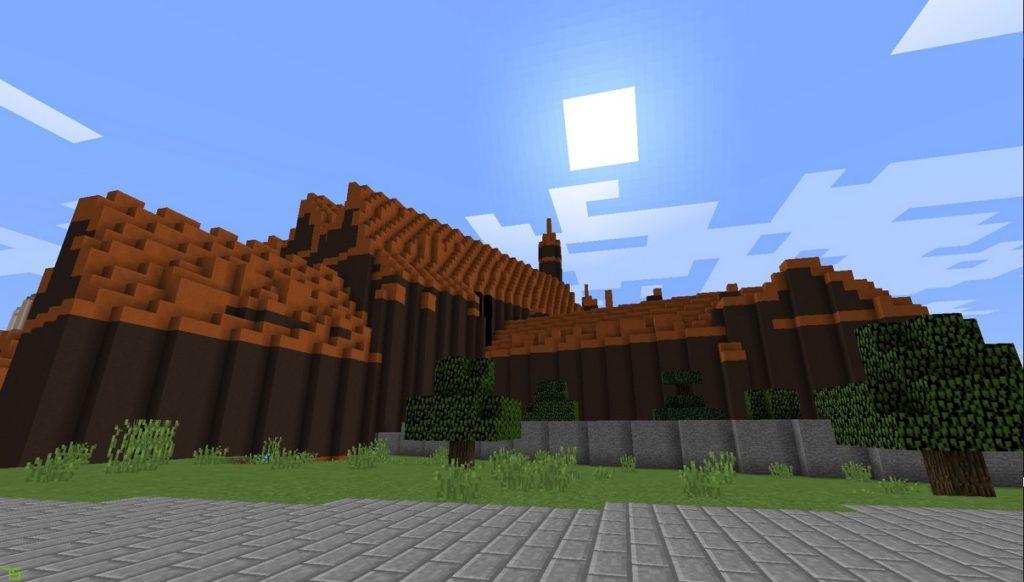Gdańsk. Muzeum Narodowe. Wizualizacja w grze Minecraft.  Na zdjęciu widać duży budynek, którego ściany są zbudowane z ciemnobrązowych bloków, a dach z jasnobrązowych. Przed gmachem znajduje się szara, brukowana droga i kilka drzew.